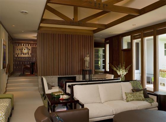 ambiente com a decoração toda em madeira, sofás em couro e mesa de madeira escura