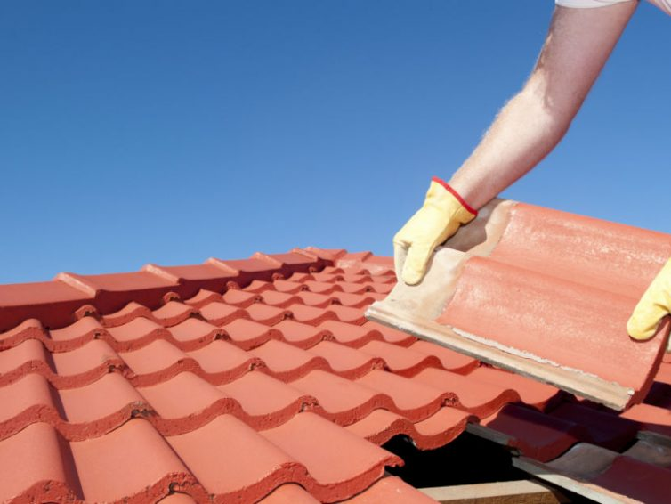 homem colocando os tipos de telha obre o telhado