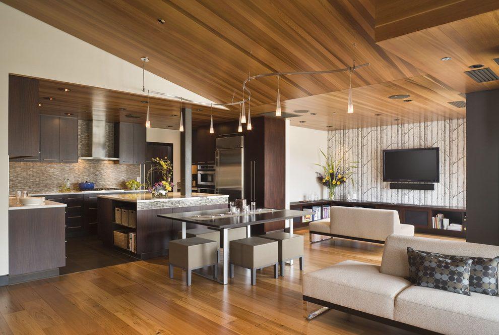 sala e cozinha com decoração em madeira com móveis de pés de metais e mesa com tampão de vidro